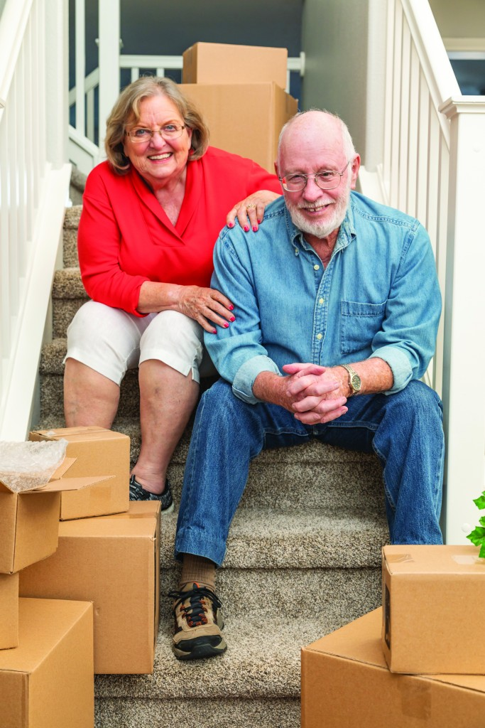 Senior,couple,resting,on,stairs,surrounded,by,moving,boxes.