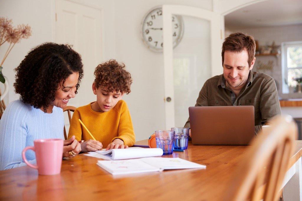 Father Works On Laptop As Mother Helps Son With Homework On Kitchen Table