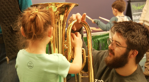 A brother shows a child how to hold an instrument to support music in our schools
