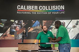Appraiser Josh Brown, left, helps a customer at Caliber Collision's Frisco auto-body and paint shop.