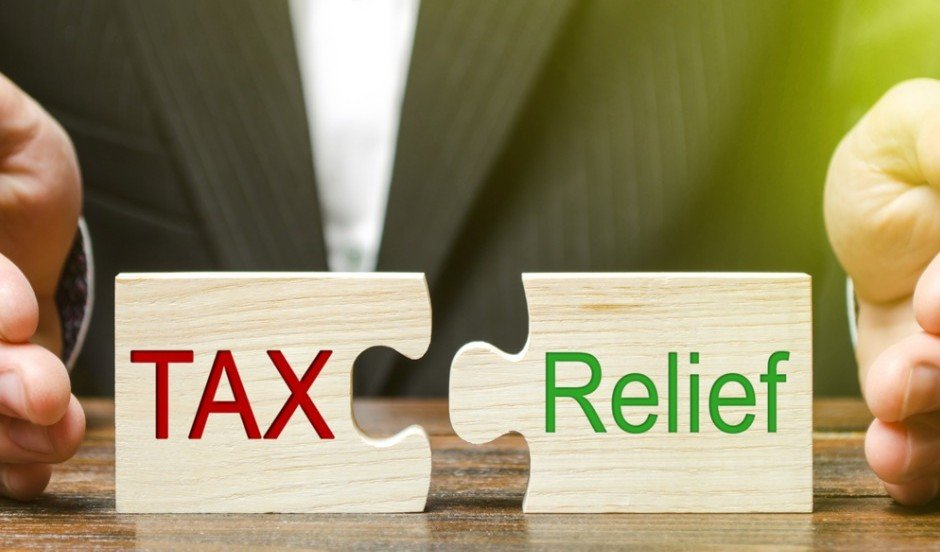 Businessman Puts Two Puzzles With The Words Tax And Relief The Of Picture Id1153812676