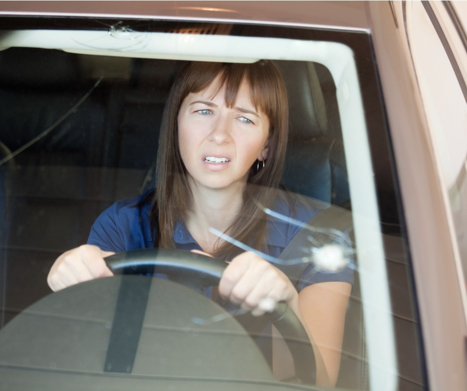 Photo Of A Young Woman Looking At Crack In Her Windshield Picture Id186668136