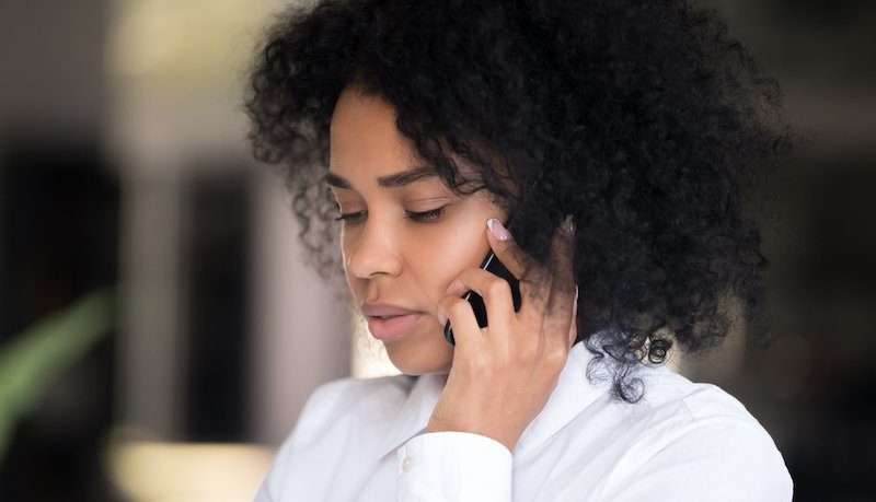 Close Up Of Thoughtful Black Woman Talk On Smartphone