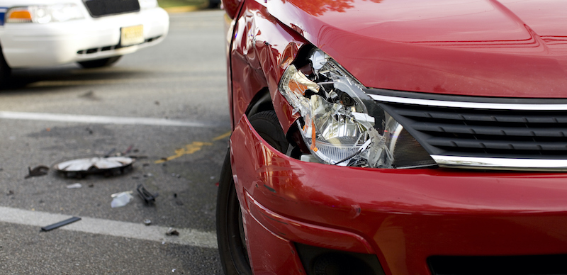 A Red Car With A Damaged Headlight After An Accident