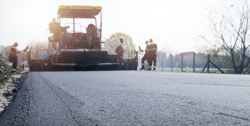 Workers Placing New Coating Of Asphalt On The Road. Road Construction.