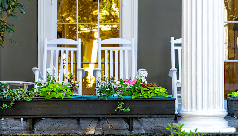 Old Street Historic Garden District In New Orleans, Louisiana With Patio Garden Green Plants Flowers, White Antebellum Column And Rocking Chairs By Mansion House