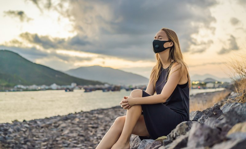 Self Isolation In Nature. Young Woman In Fashionable Black Medical Mask With Filter Sitting By The River. Coronavirus 2019 Ncov Epidemic Concept. Portrait Of A Woman With Expressive Eyes During A Virus Or Disease Epidemic Of