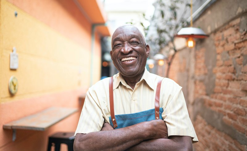 Portrait Of Smiling Elderly Waiter Looking At Camera