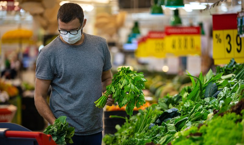 Alarmed Male Wears Medical Mask Against Coronavirus While Grocery Shopping In Supermarket Or Store Health, Safety And Pandemic Concept Young Man Stockpiling Food In Fear Of Covid 19