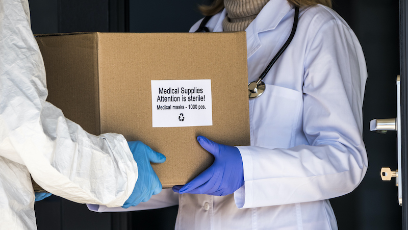 A Person In A Protective Suit Is Handed A Box With Protective Medical Masks To The Doctor