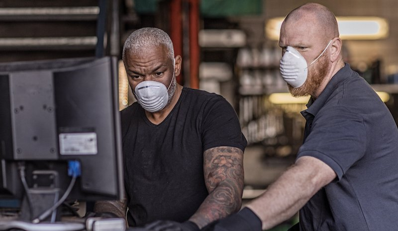Two Male Mechanic Essential Workers Wearing A Face Mask Each During Virus Outbreak