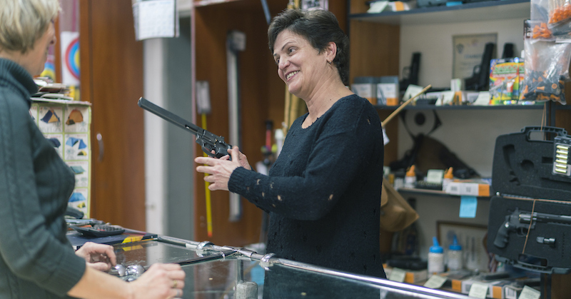The Mature Blonde Woman Buying The Revolver In The Small Gun Store