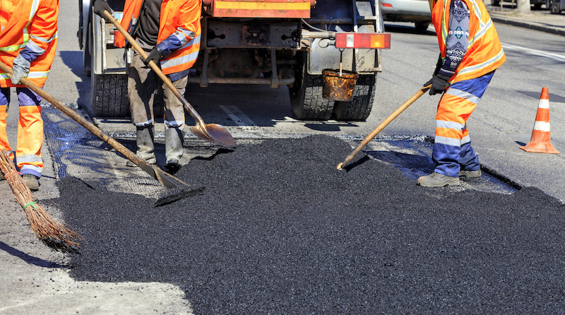The Working Team Smoothes Hot Asphalt With Shovels By Hand When Repairing The Road.