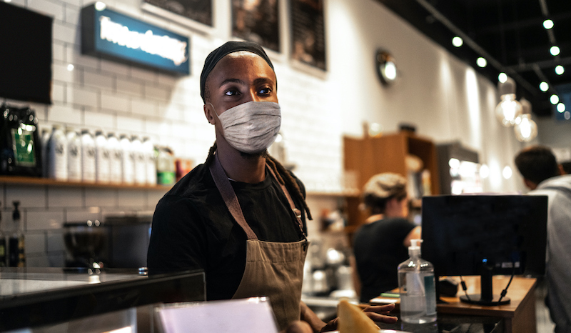 Young Waiter With Face Mask Working In Coffee Shop