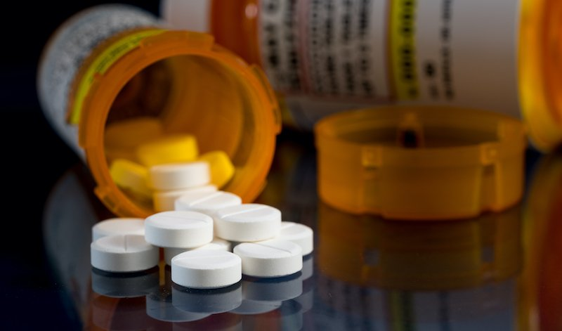Macro Of Oxycodone Opioid Tablets With Prescription Bottles Against Dark Background