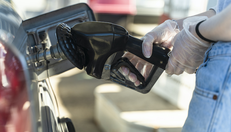 Young Caucasian White Long Haired Woman Refueling A Car At The Gas Station. Close Up View Of Her Hand. She Wearing Protective Latex Gloves Because Of The Coronavirus Pandemic.