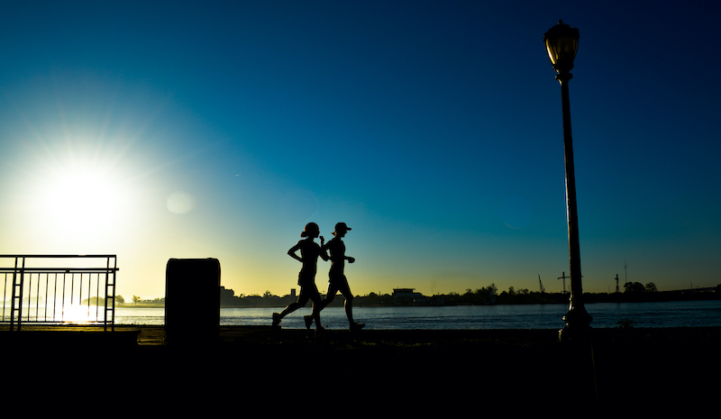 Silhouette Of Joggers Along Mississippi