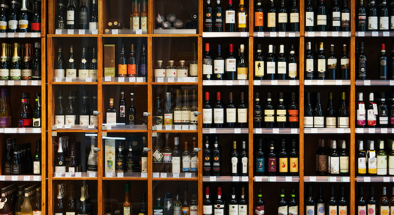 Large Cabinet With Many Bottles Of Wine At Supermarket