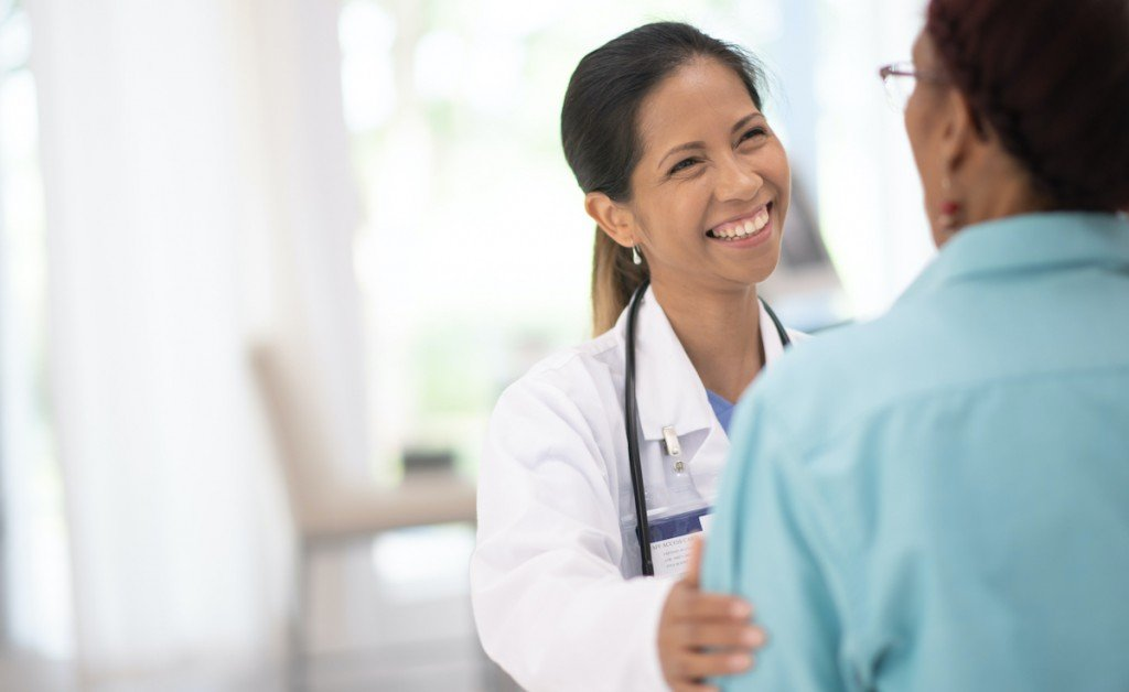 An Elderly Woman In Her Doctors Office Receiving A Check Up Stock Photo