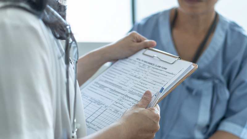 Patient Health Insurance Claim Form In Doctor Or Nurse Hands For Medicare Coverage And Medical Treatment From Illness, Accident Injury And Admitted In Hospital Ward