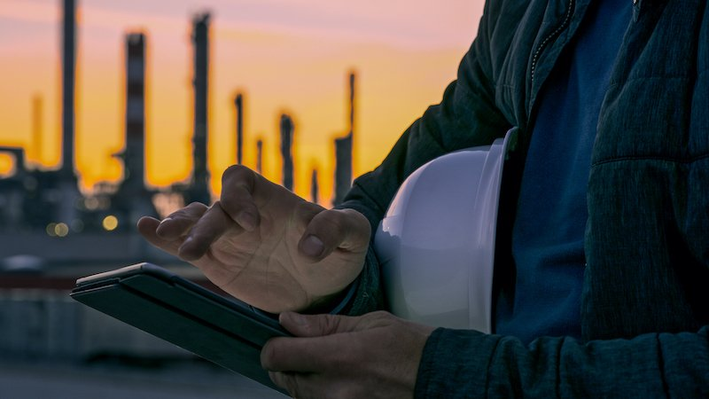 Close Up Of Engineer Using Tablet Near Oil Refinery.