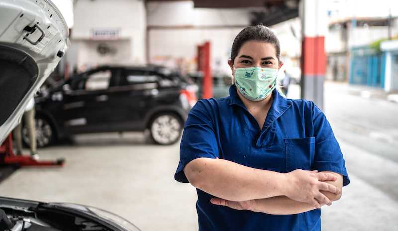 Portrait Of Auto Mechanic Woman With Face Mask At Auto Repair Shop