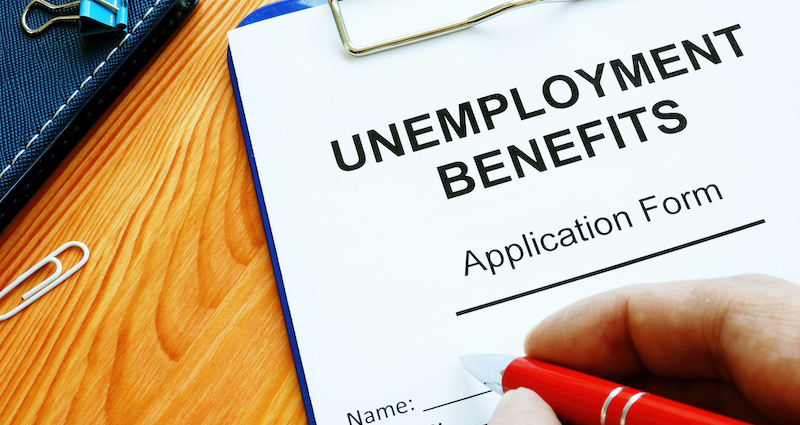 Man Fills In Unemployment Benefits Application Form.