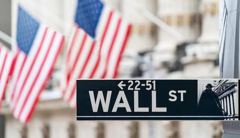 Wall Street Sign In New York City Financial Economy And Business District With America National Flag Background. Stock Market Trade And Exchange Zone.
