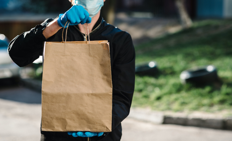Courier In Protective Mask, Medical Gloves Delivers Takeaway Food. Employee Hold Cardboard Package. Place For Text. Delivery Service Under Quarantine, 2019 Ncov, Pandemic Coronavirus, Covid 19.