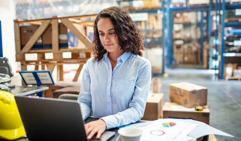 Businesswoman Updating Stocks On Laptop At Warehouse