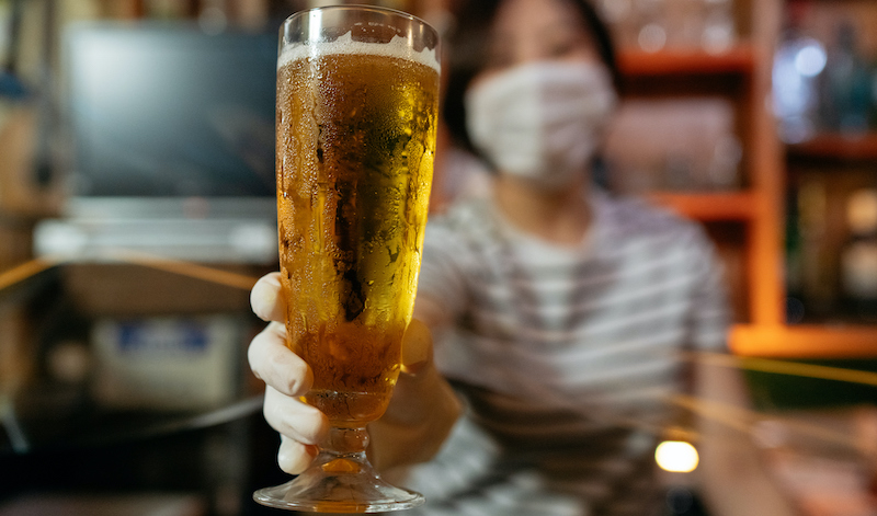 Bar Owner Serving Beer With Protective Plastic Glove From Behind Protective Plastic Curtain
