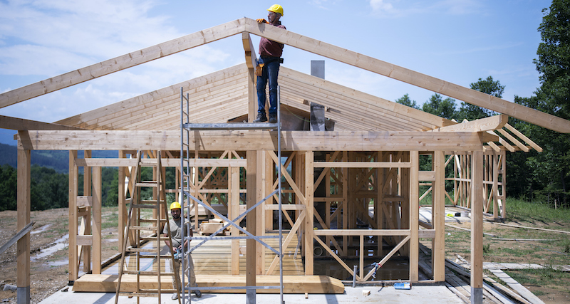 Construction Workers Working On Wooden Roof Of House.