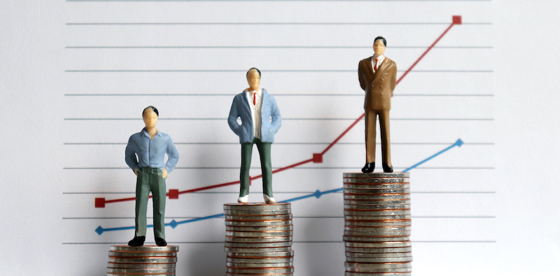 Miniature People Standing On A Pile Of Coins In Front Of A Graph. The Concept Of The Difference Between Occupation And Income.