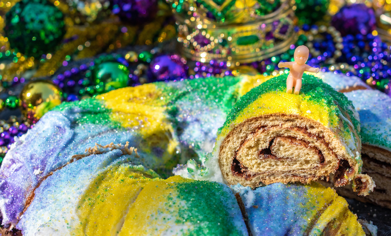 Sliced Mardi Gras King Cake Topped With Toy Baby
