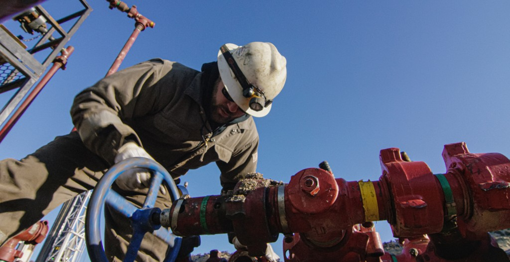 An Oilfield Worker In His Thirties Pumps Down Lines At An Oil And Gas Drilling Pad Site On A Cold, Sunny, Winter Morning