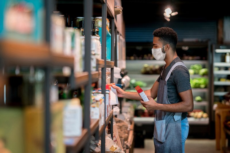 Man Working At A Supermarket Restocking The Shelves And Wearing A Facemask