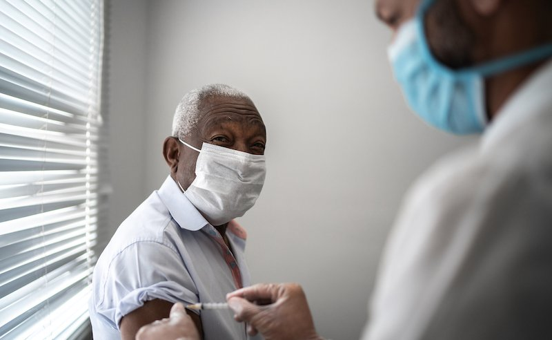Nurse Applying Vaccine On Patient's Arm Using Face Mask