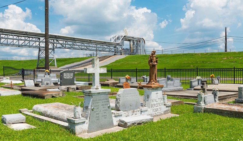 View Of The Holy Rosary Cemetery In Taft, Louisiana, With A Pipeline On The Background.