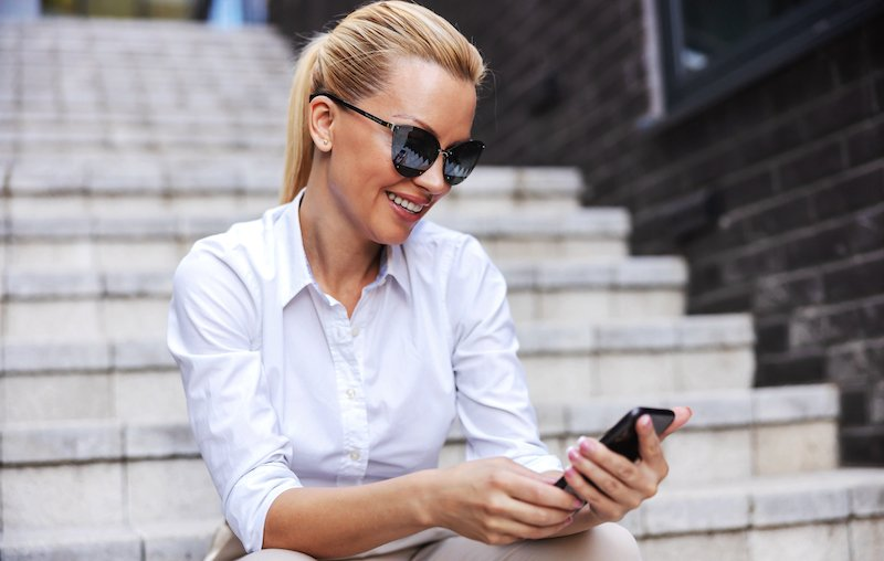 Glamorous Attractive Fashionable Blond Woman With Sunglasses Sitting On The Stairs Outdoors And Using Smart Phone.
