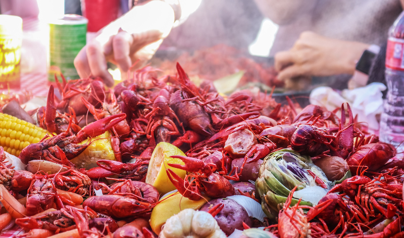 Boiled Crawfish And Vegetables Piled On Red Checked Tablecloth With Eating Tray And Arm Of Person Eating Bokeh Behind Shallow Focus