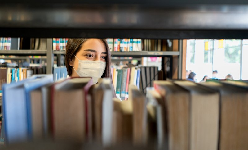 Student Wearing A Facemask At The Library While Looking For A Book