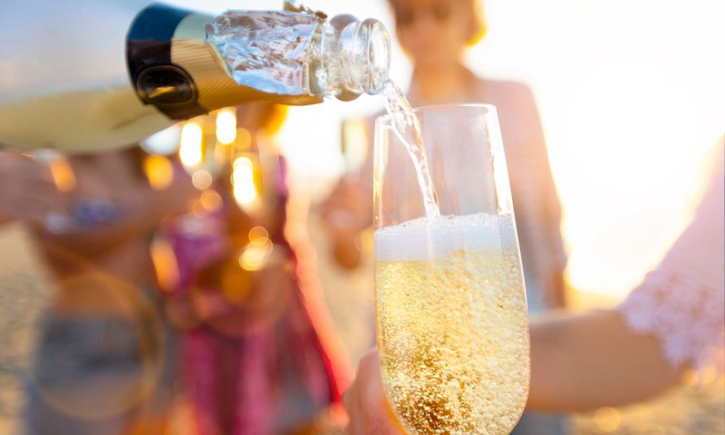 Pouring A Glass Of Champagne With People Partying In The Background.