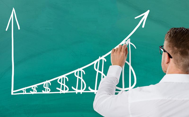 Businessman Drawing Increasing Dollar Graph