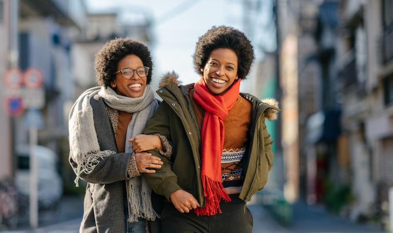 Black Twin Sisters Walking In Street Arm In Arm Happily