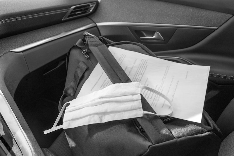 Travel Black Bag, Permit Document And Personal Protective Mask In The Car. Concept Of Escape Or Leaving Home, Hotel. Baggage Of A Person Running Away From A Virus, Pandemic, Black And White Photo.