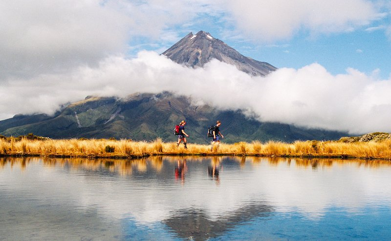 Hikers Reflection Of Mount Taranaki Egmont In Natural Lake Middle