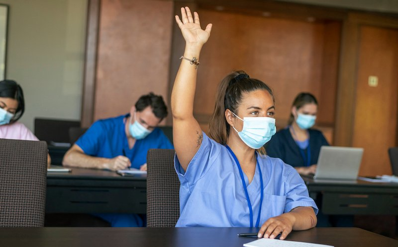 Female Medical Student Raising Hand In Class
