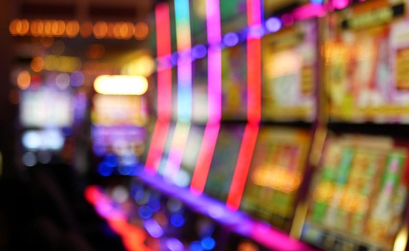 Defocused Slot Machines Glow In Casino On Fabulous Las Vegas Strip, Usa. Blurred Gambling Jackpot Slots In Hotel Near Fremont Street. Illuminated Neon Fruit Machine For Risk Money Playing And Betting
