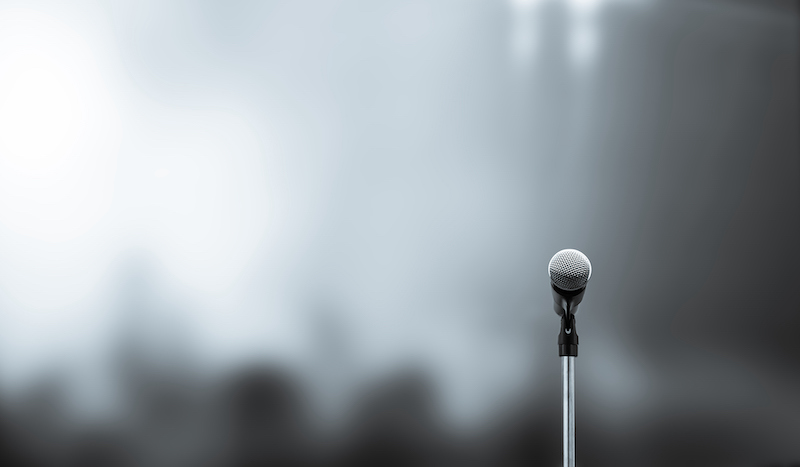 Close Up The Microphone On Stand For Speaker Speech Presentation Stage Performance With Blur And Bokeh Light Background.