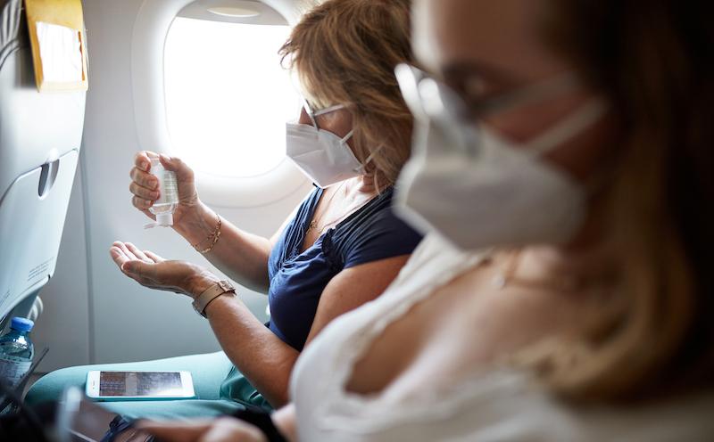 Mature Woman Using Hand Sanitizer During Airplane Trip